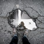 reflection of city buildings in pothole with person standing on asphalt